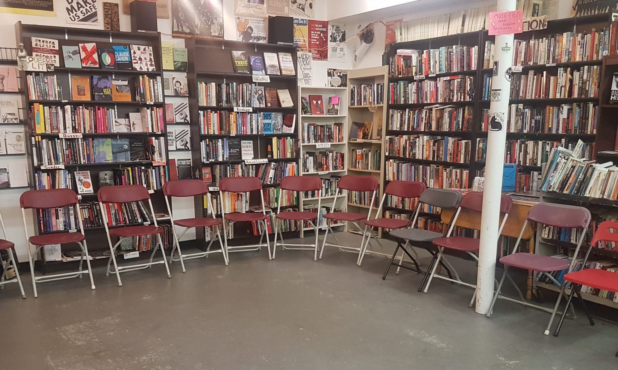 Image of store setup for an event. A circle of about a dozen folding chairs. Behind them are bookcases and the walls are decorated with posters.