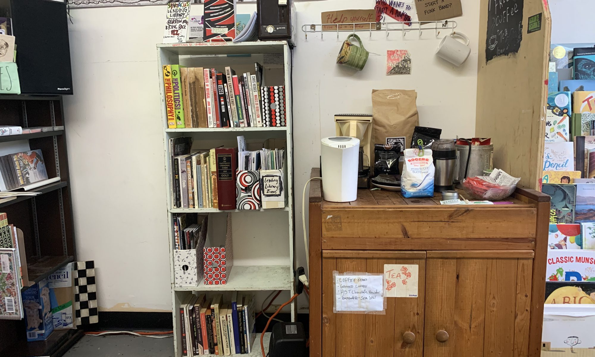 Spartacus lending library. Small white bookcase with 4 shelves of books. A toaster and more books are on top. To the right is a low cabinet with supplies for making coffee and tea.