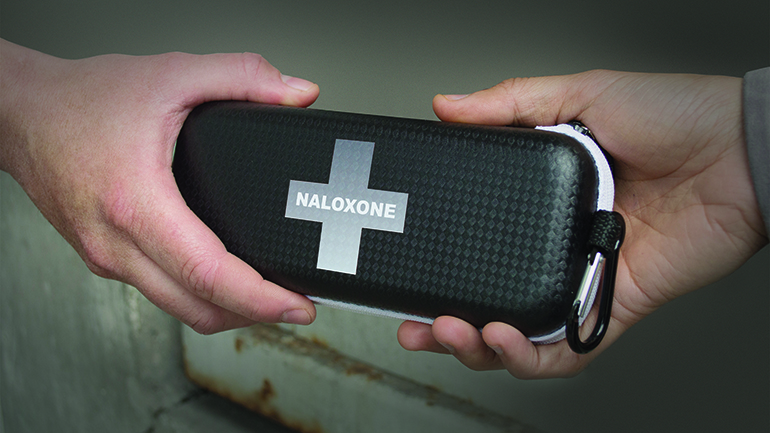Image of a naloxone kit being passed between two people's hands.